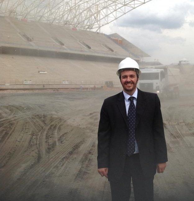 """Para cego """"ver"""": Foto mostra o Conselheiro Heroi Vicente, trajando terno, gravata e usando um capacete de obra, durante a construção da Arena Corinthians. Heroi está sorrindo e, ao fundo, em uma ambiente cheio de poeira, vê-se a arquibancada da Arena Corinthians em construção. Heroi estava onde hoje é o gramado da Arena. Na foto, o piso ainda é de terra e lama, com um caminhão da obra parado ao fundo."""